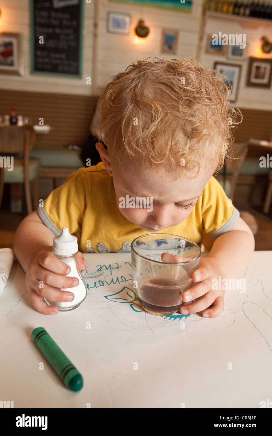 Three year old boy waiting for his food in fish and chip shop, Dartmouth Devon, England, United Kingdom. Stock Photo