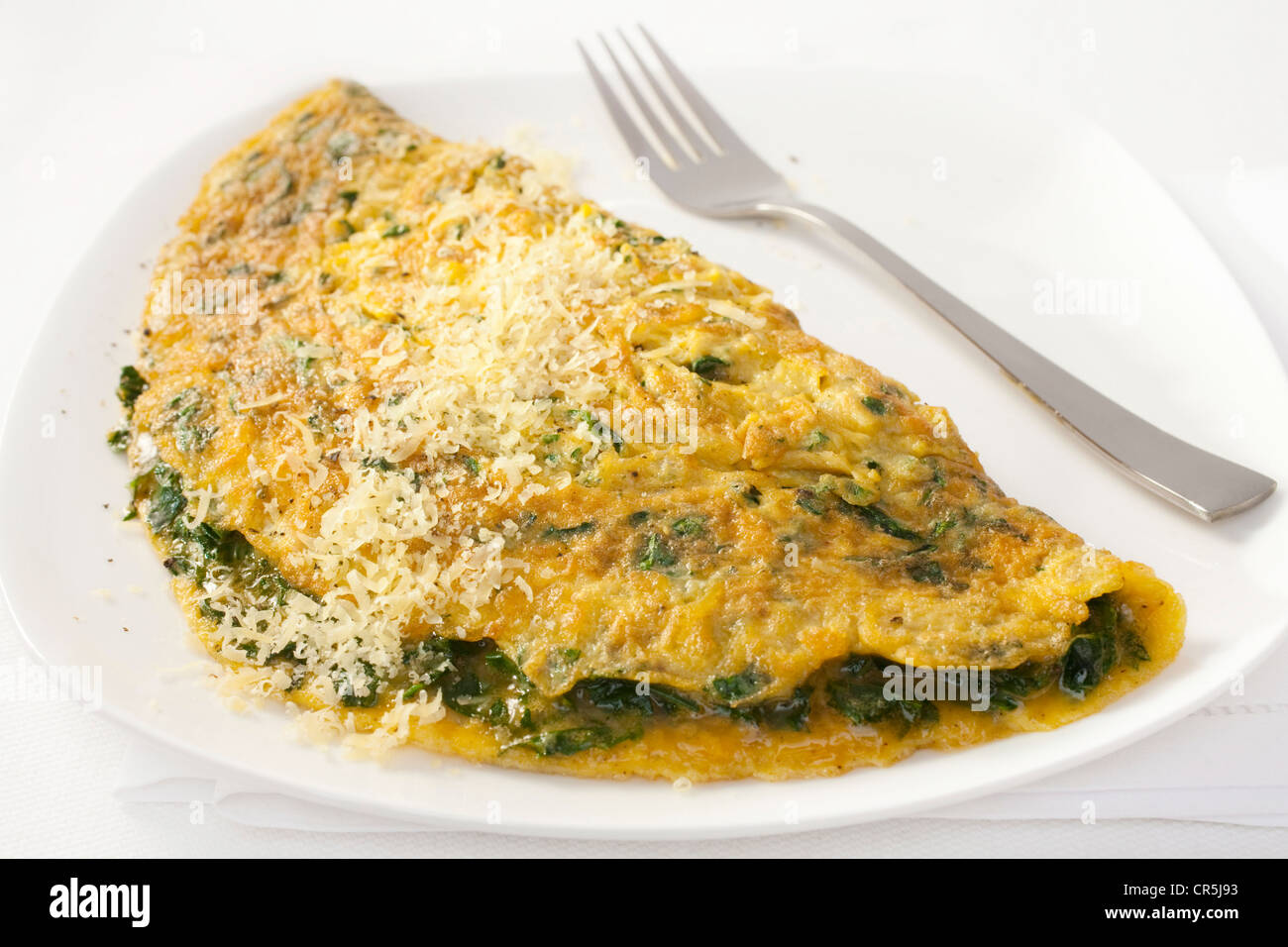 A French omelet cooked with spinach and parmesan, sprinkled with parmesan. - Stock Image