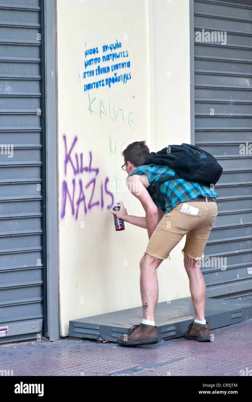 Anti nazi graffiti. Guy writing with spray on the wall ' Kill nazis' - Stock Image