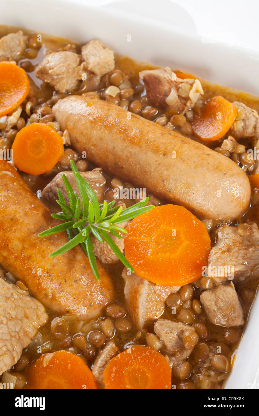 Tasty French or Spanish style stew with lentils, pork, sausages and carrots, Stock Photo