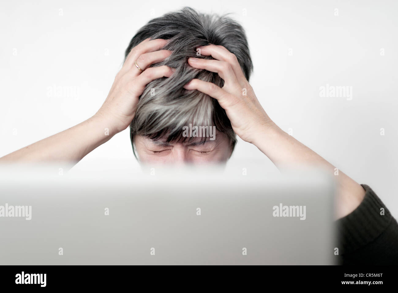 stressed woman sitting behind a computer screen tearing at her hair