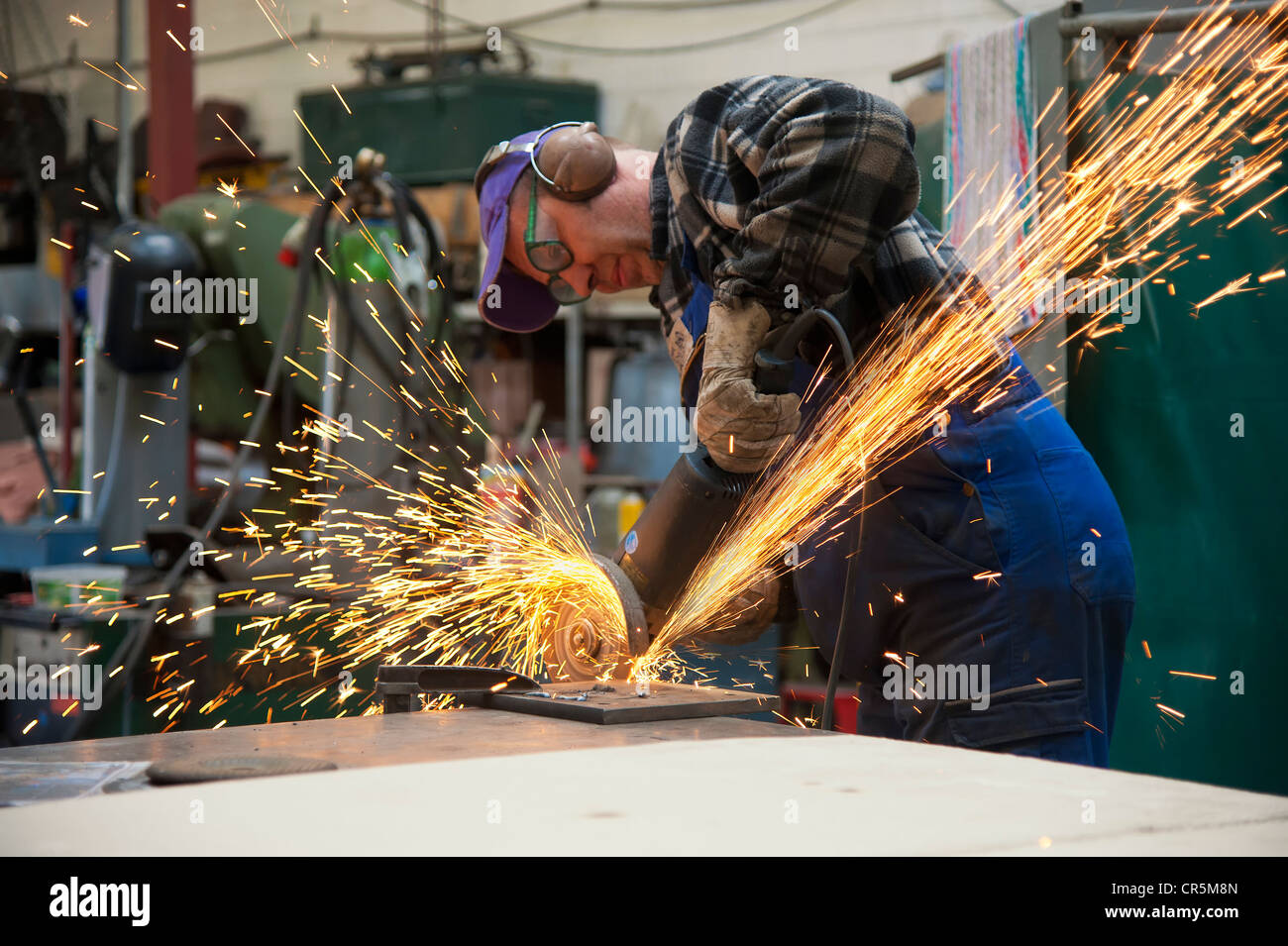 Craftsmen working with an angle grinder in his workshop - Stock Image