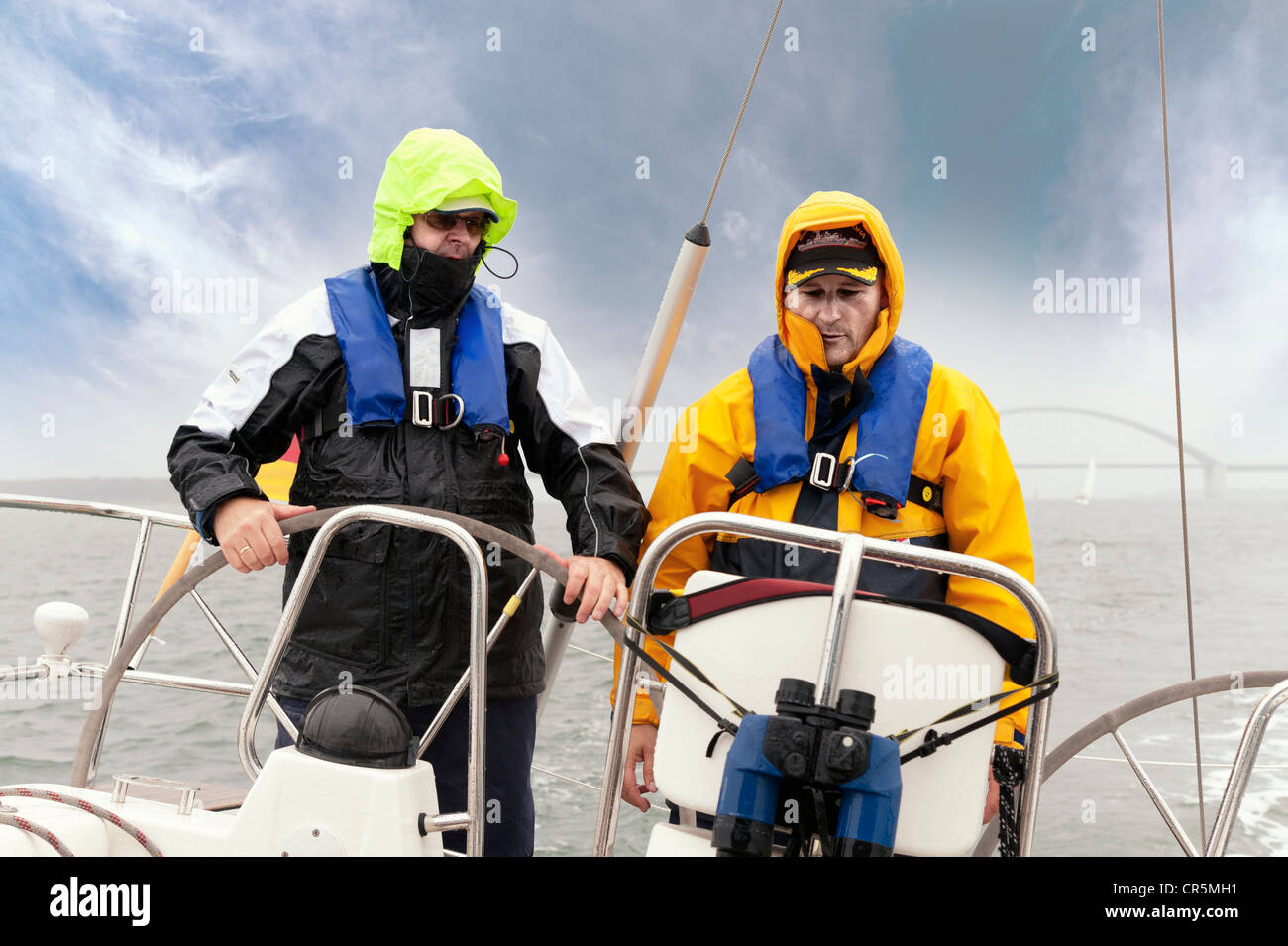 Two men standing on the stern of a yacht Stock Photo