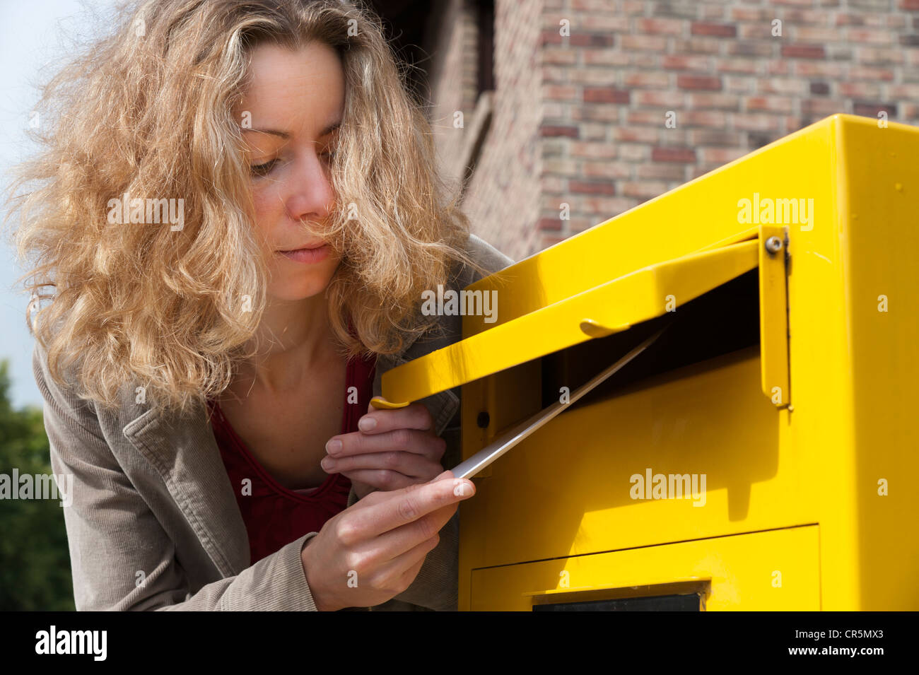 Young woman putting letter into a postbox - Stock Image