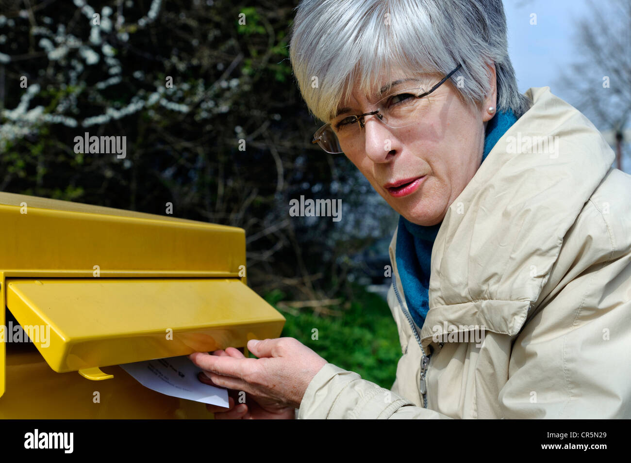 Woman putting a letter into a mailbox, Germany, Europe - Stock Image