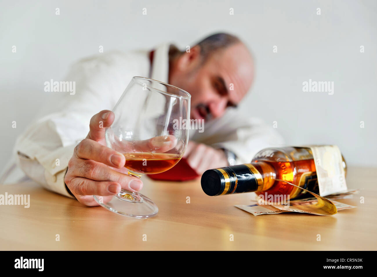 Alcohol addict holding a cognac glass, sitting with a bottle of alcohol at a table - Stock Image