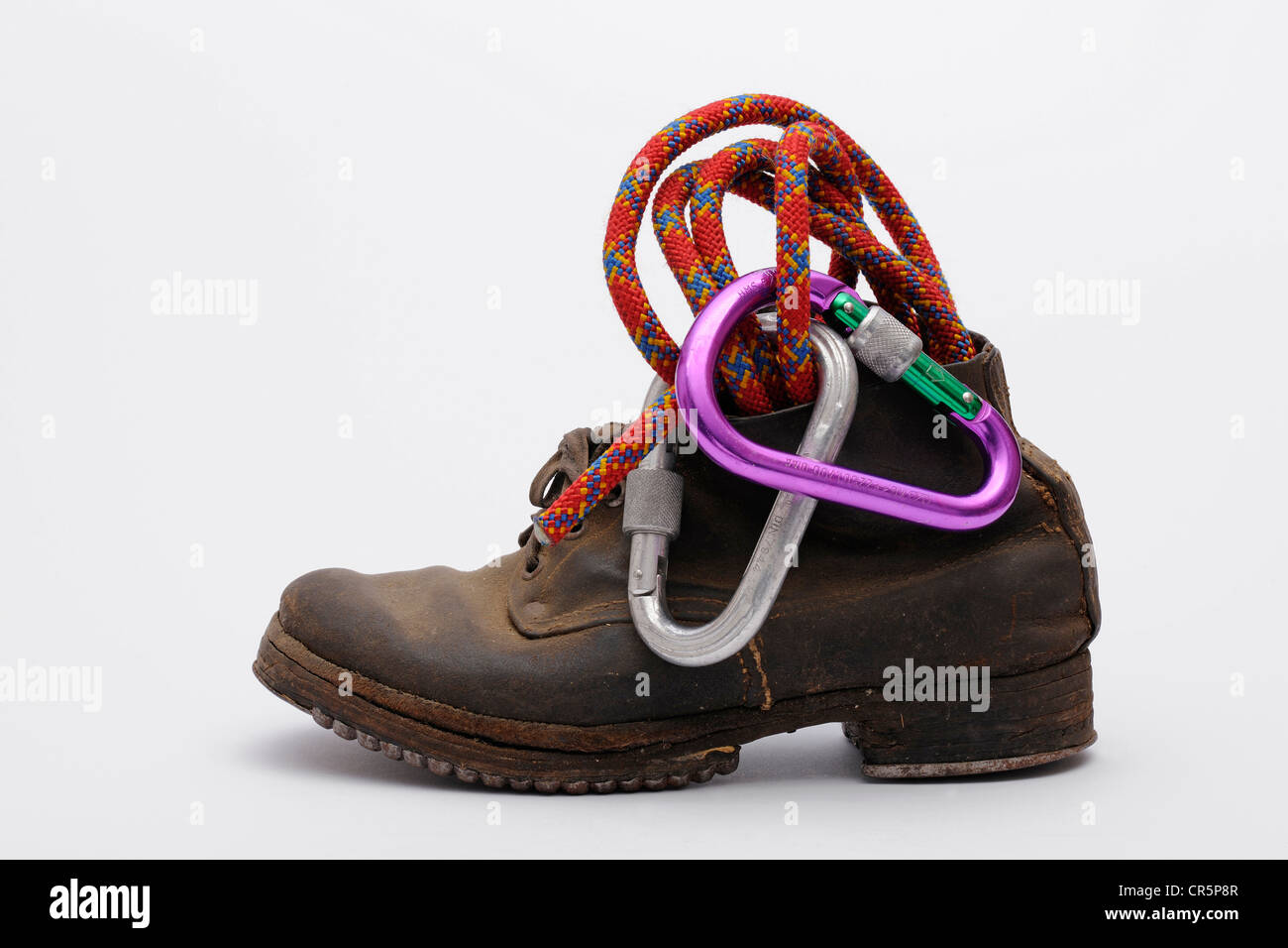 Old mountain boots with nailed soles and iron heels, with a climbing rope and carabiner - Stock Image