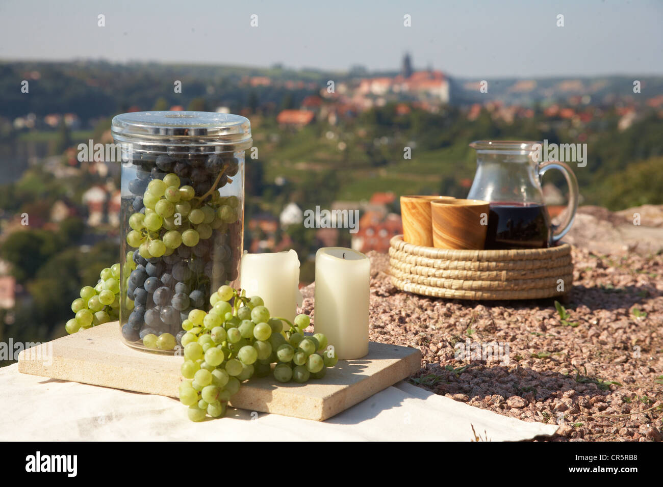 Still life with wine, grapes, a wine decanter, wine cups and candles, against the backdrop of Meissen, Saxony, Germany, - Stock Image