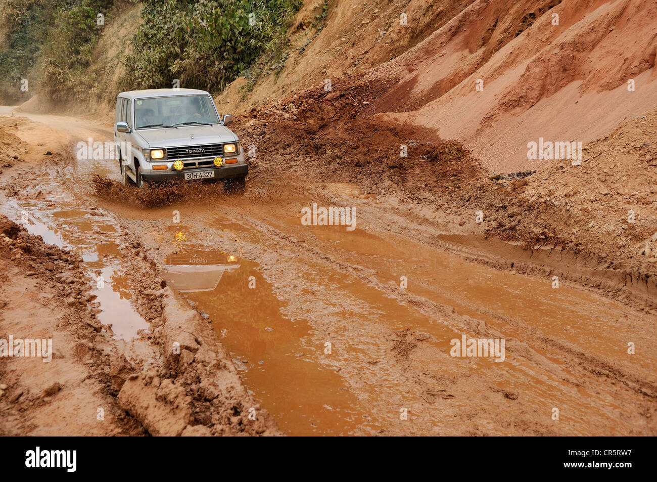 Toyota Land Cruiser driving on a muddy road through puddles, Vietnam, Asia - Stock Image