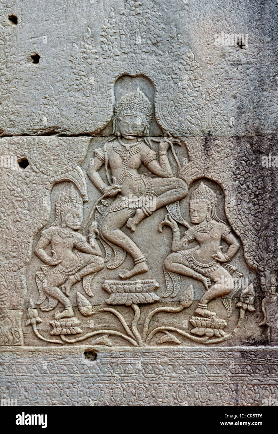 Stone bas-relief of a group of three apsaras dancing on lotuses, Bayon Temple, Angkor Thom, Siem Reap, Cambodia, - Stock Image