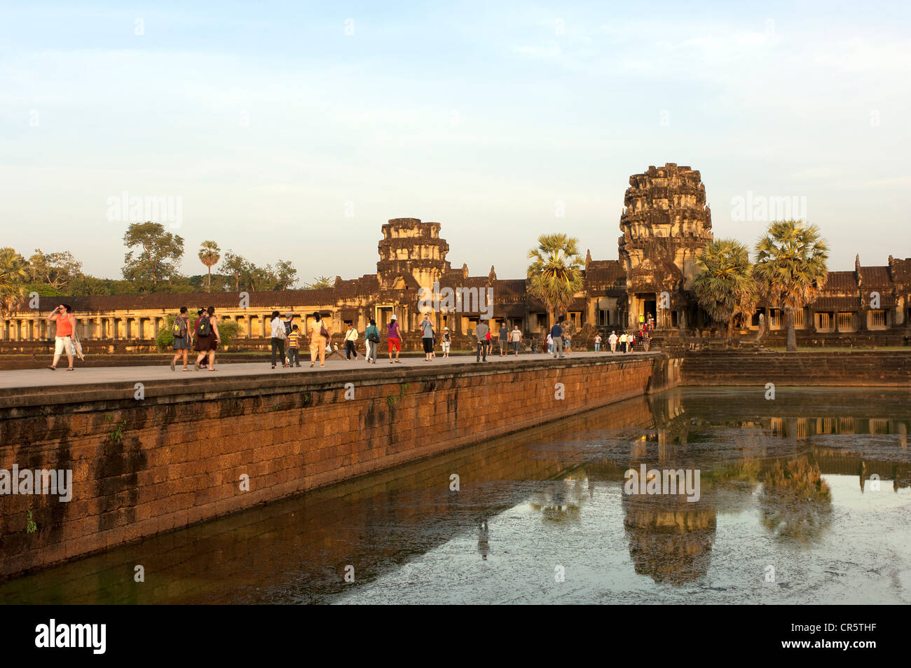 View across the castle bridge on the west wing of the Angkor Wat temple complex in the evening light, , Cambodia, - Stock Image
