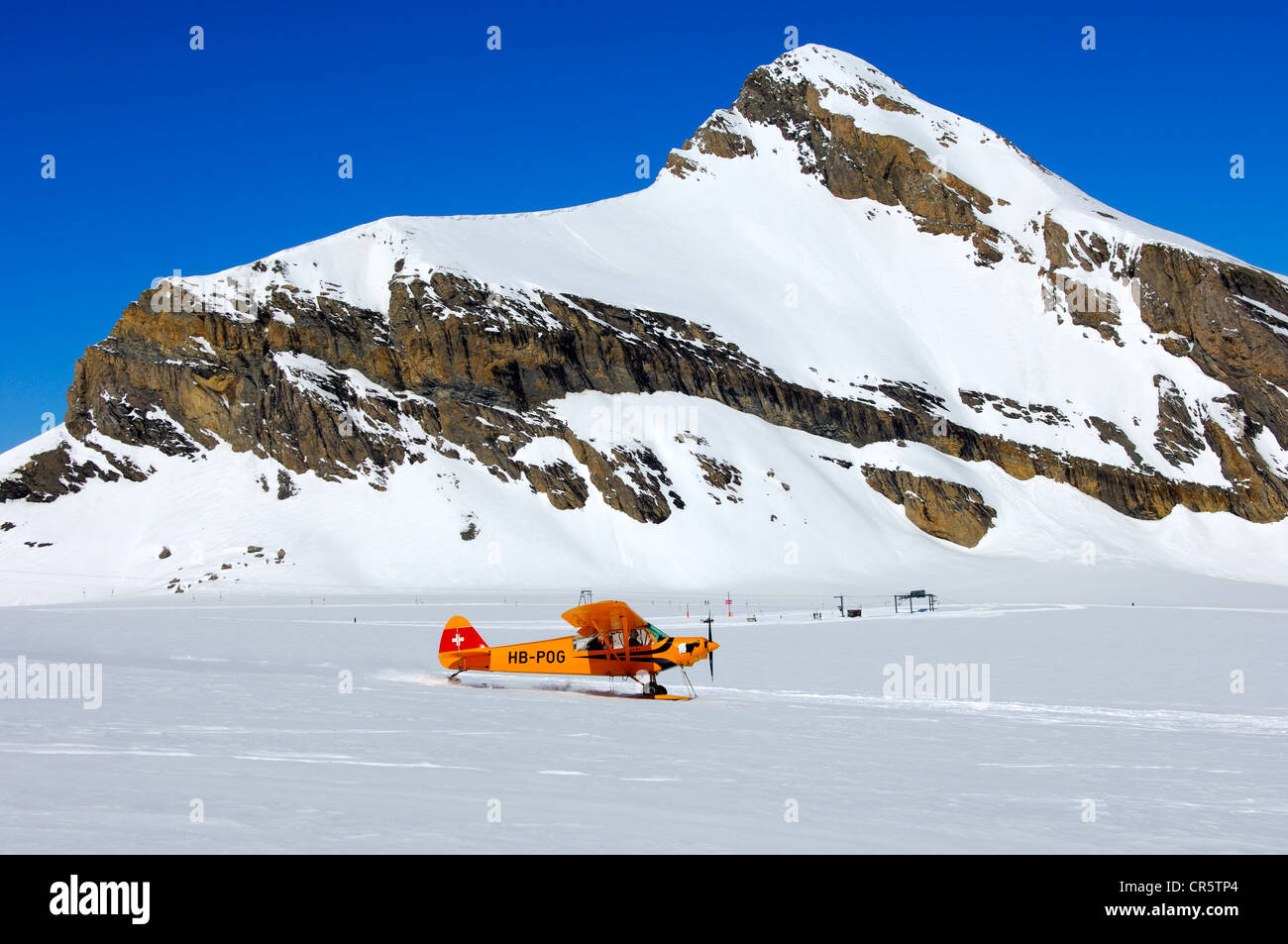 Takeoff of a Piper PA-18 Super Cub on the snow-covered Glacier de Tsanfleuron mountain airfield at the foot of Oldenhorn - Stock Image