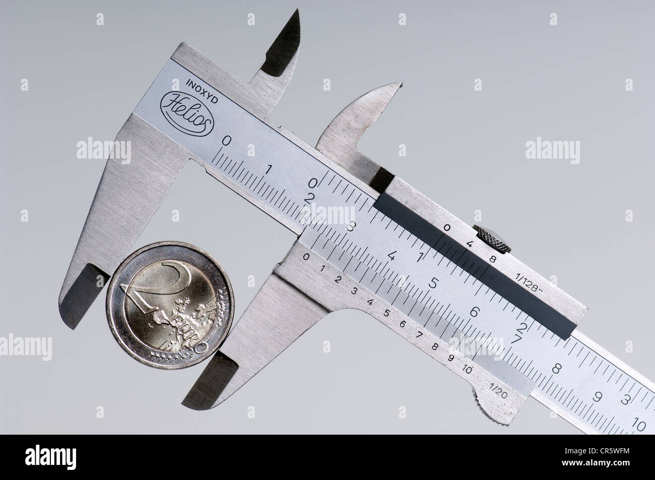 Two-euro coin in calliper, symbolic image for the euro under pressure - Stock Image