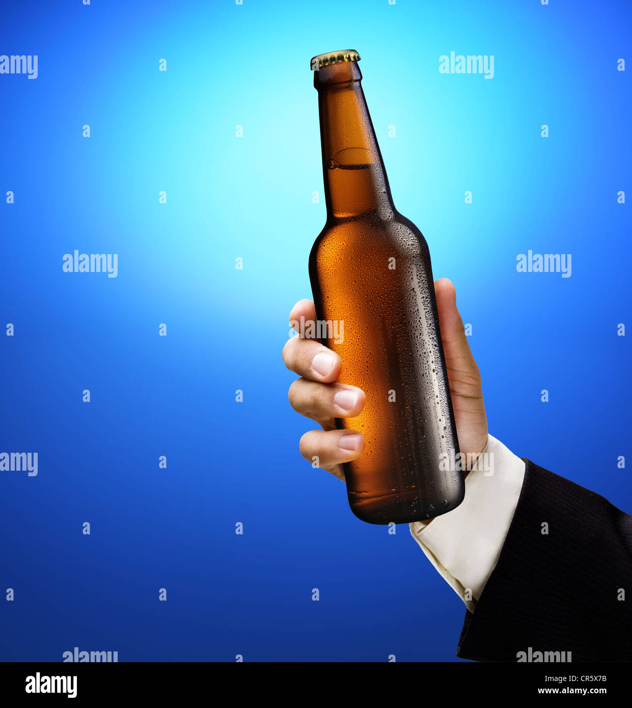 Bottle of beer in a man's hand on a blue background. Stock Photo