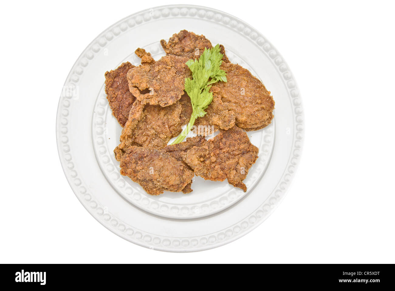 Chicken cutlet served on a plate and decorated with parsley leaf - Stock Image