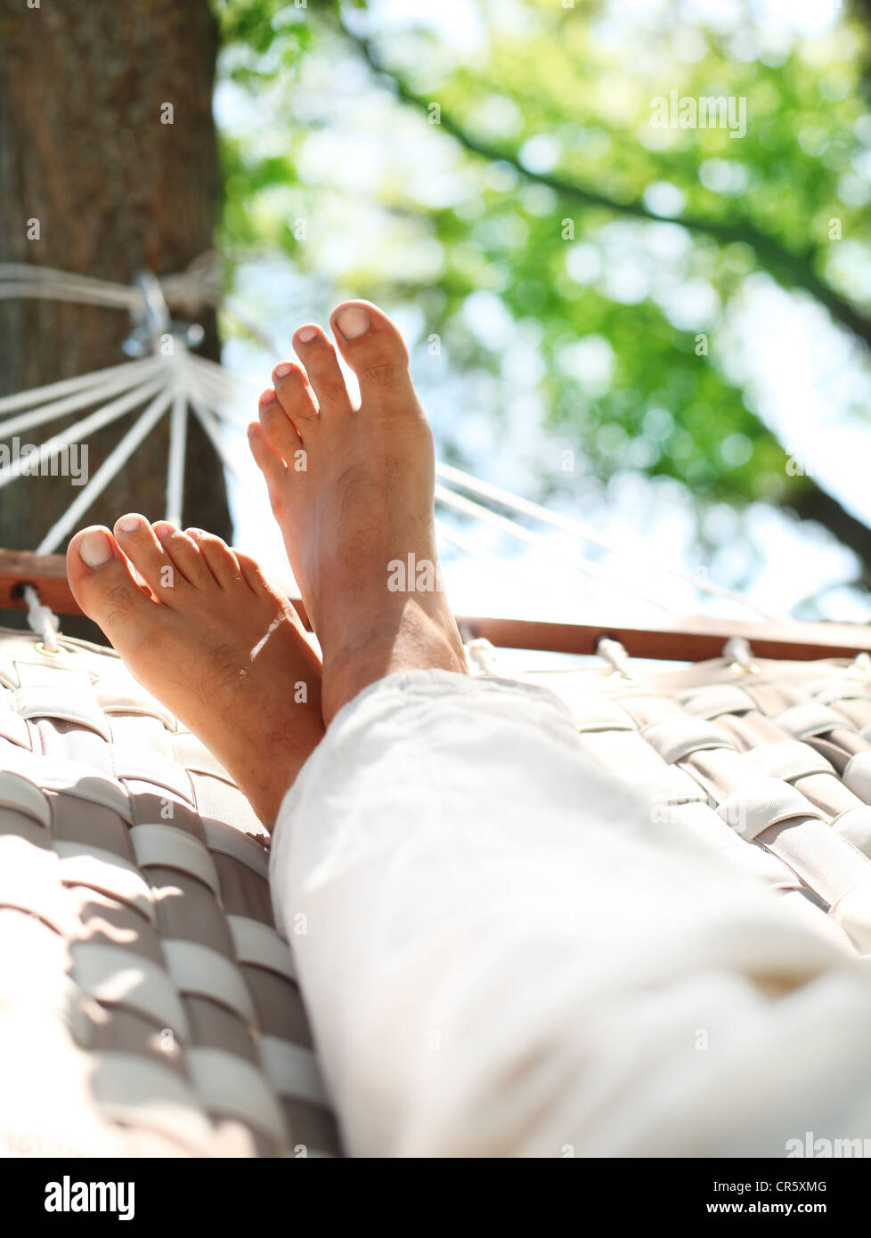 Feets in a hammock on a summer nature background. - Stock Image
