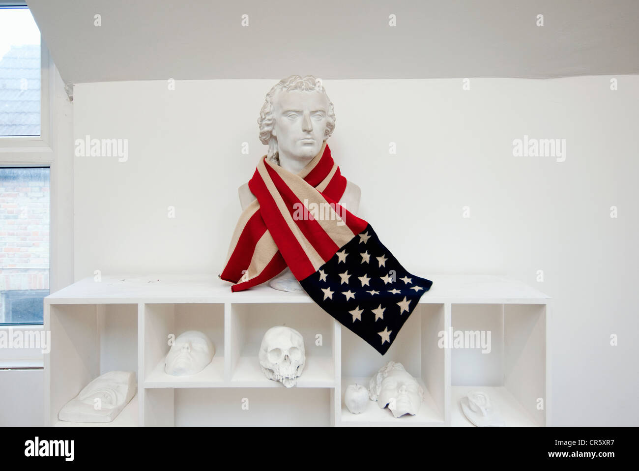 A Stars and Stripes American scarf draped around an anonymous bust in an artist's studio. - Stock Image