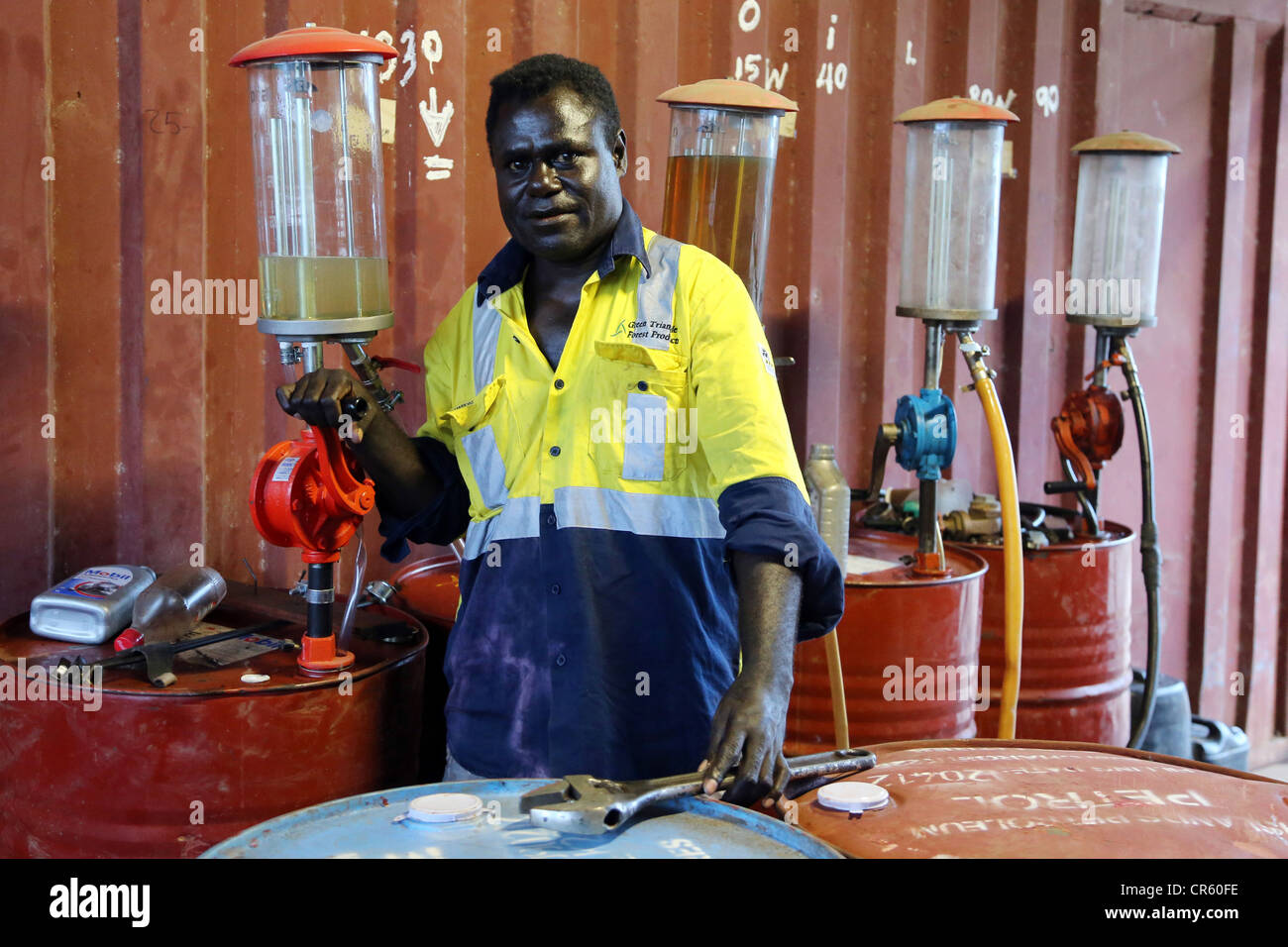 Fuel station owner stands between petrol barrels, Arawa, Autonomous Region of Bougainville, Papua New Guinea Stock Photo