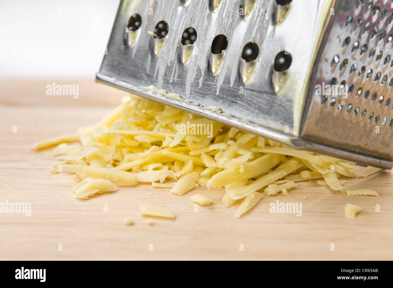 Grated cheese with grater on wooden chopping board against white background - Stock Image