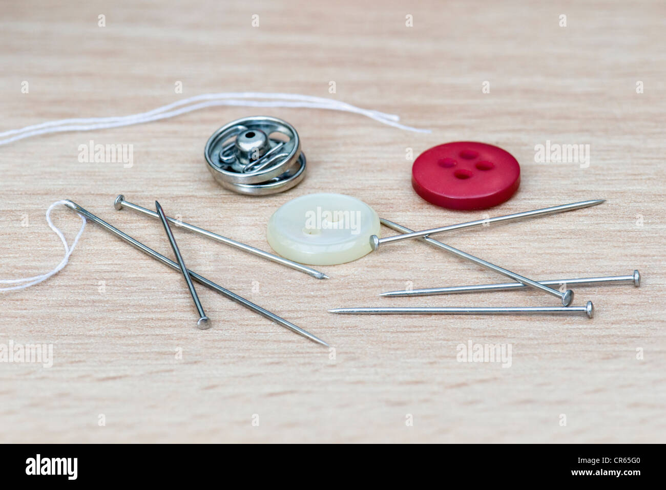 Sewing implements on wooden table including needle and thread, pins, popper and buttons - Stock Image