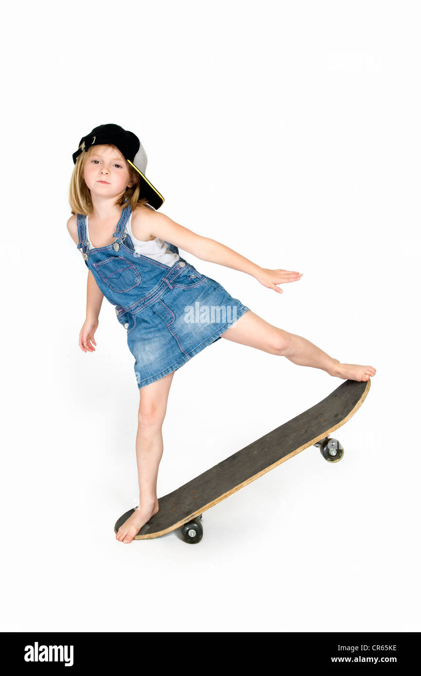 Studio image of Caucasian 7 year old girl in denim clothing balanced on a skateboard on a white background - Stock Image