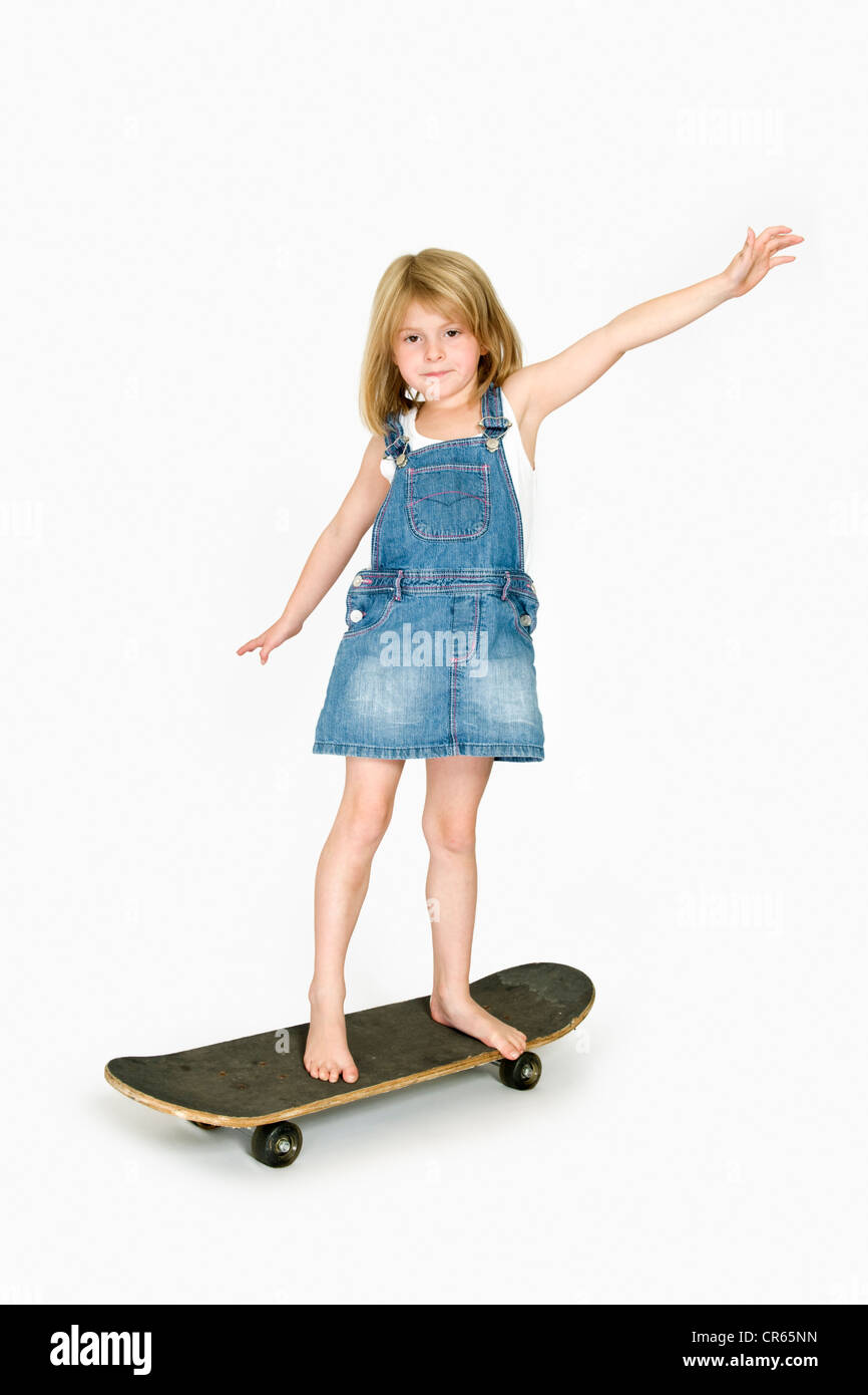 Studio image of Caucasian 7 year old girl in denim clothing with skateboard on a white background with arms out - Stock Image