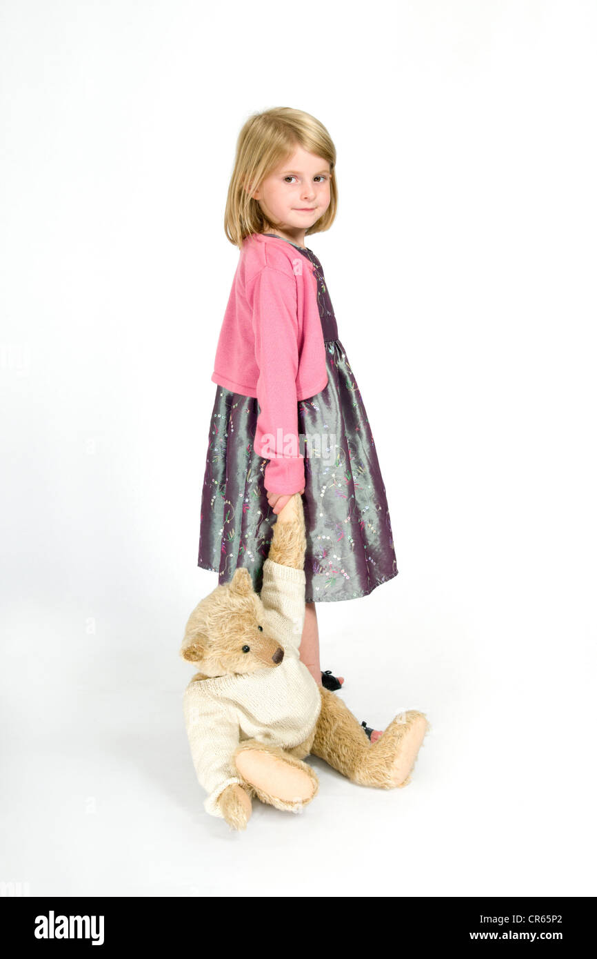 Studio image of a happy Caucasian 7 year old girl with teddy bear on a white background - Stock Image