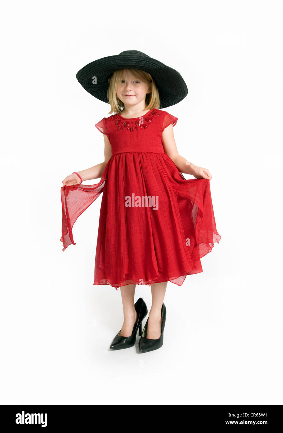 Studio image of Caucasian 7 year old girl in red dress playing dress up on a white background - Stock Image
