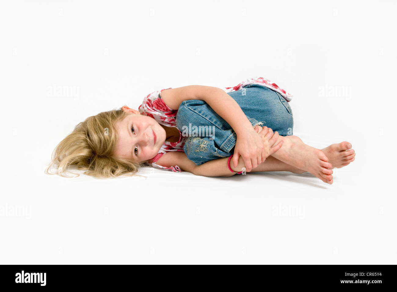 Studio image of Caucasian 7 year old curled up on a white background with a happy expression on her face - Stock Image