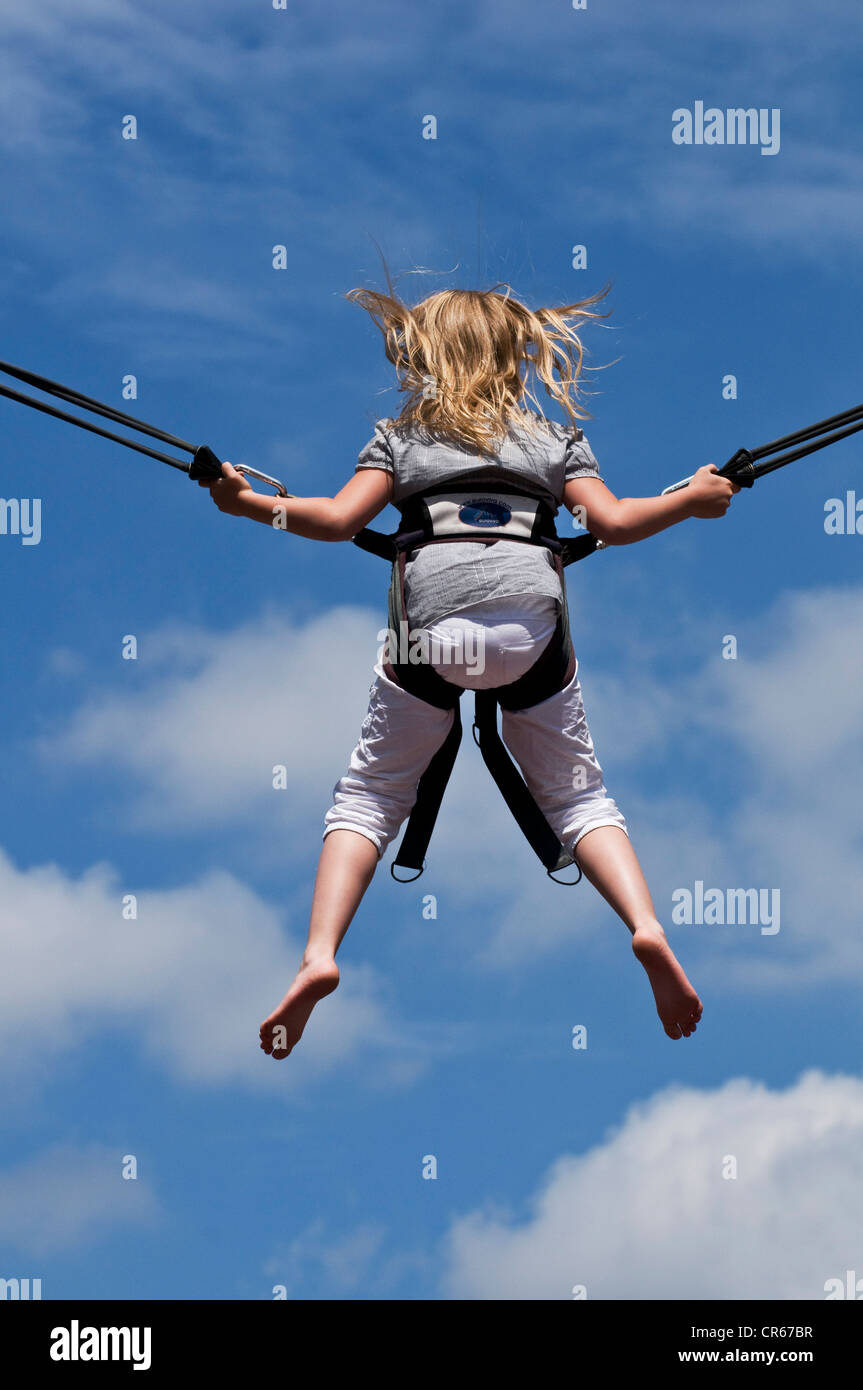 Girl jumping on a trampoline with a safety harness, back side, North Rhine-Westphalia, Germany, Europe - Stock Image