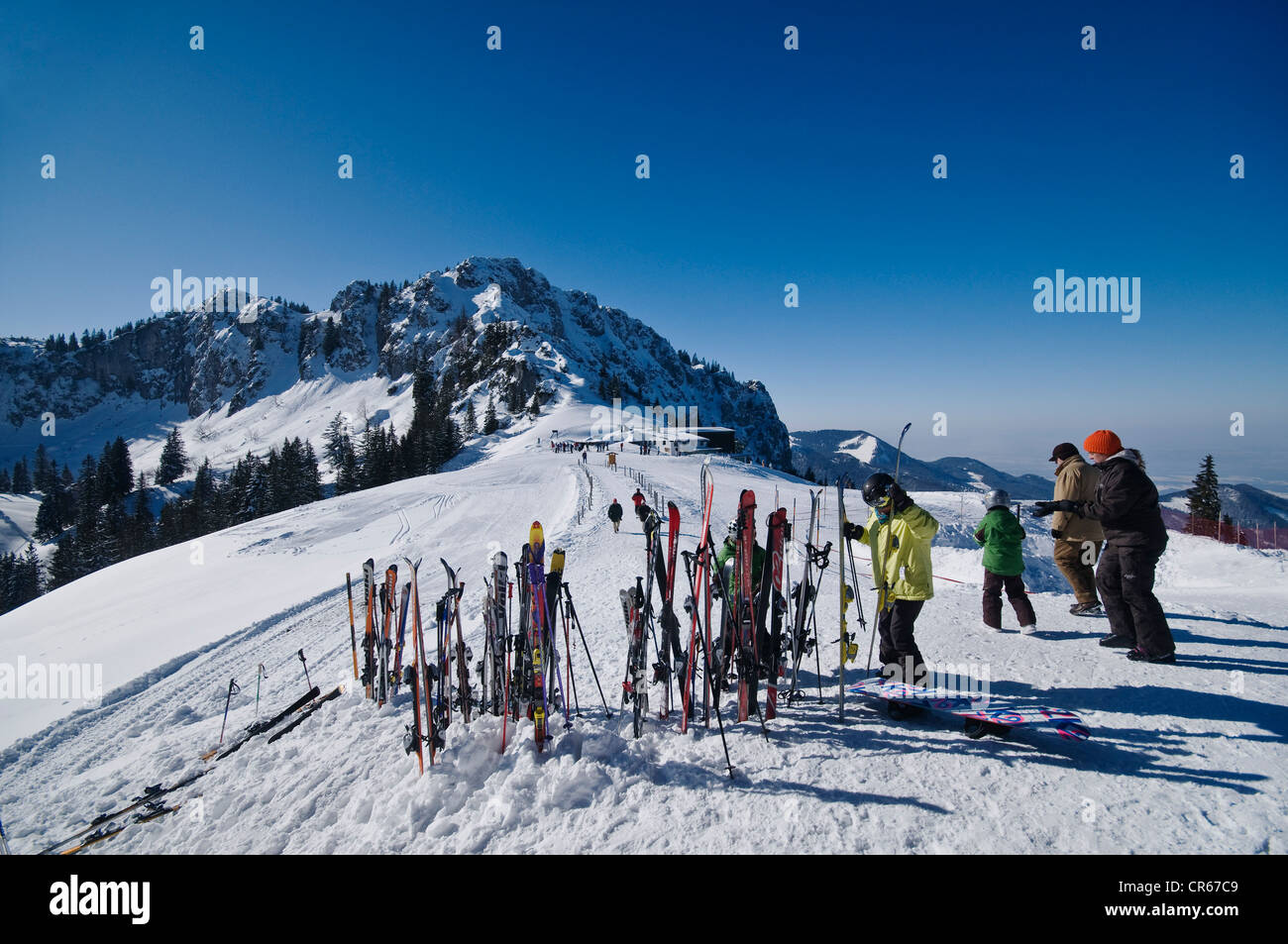 Mountain station 'Kampenwandbahn', with skis upright in the snow, skiers fetching their skis, Aschau, Chiemgau - Stock Image