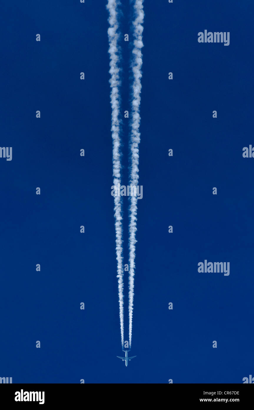 Aircraft with two contrails against a blue sky - Stock Image
