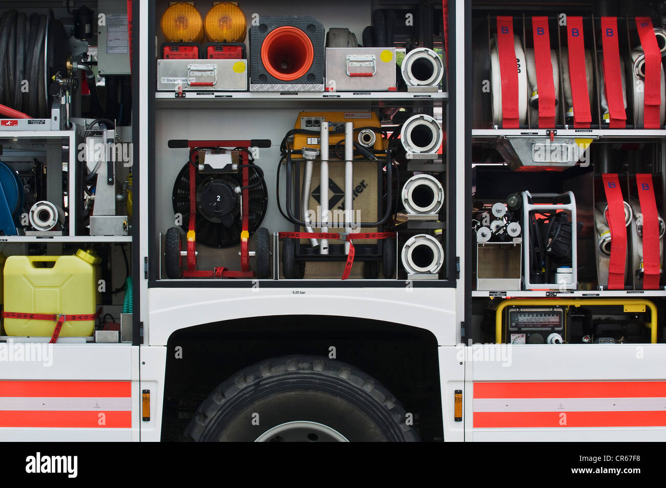 Stocked tool and gear wagon of the fire service, container, generator, cable reel, pump, warning lights, hose fittings, - Stock Image