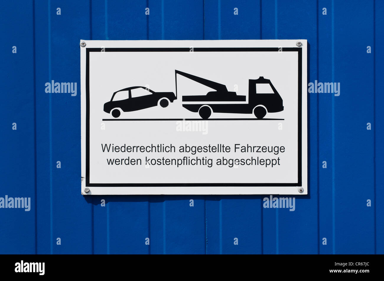 No parking sign with a pictogram and a message in German with a spelling mistake, Wiederrechtlich should be Widerrechtlich - Stock Image