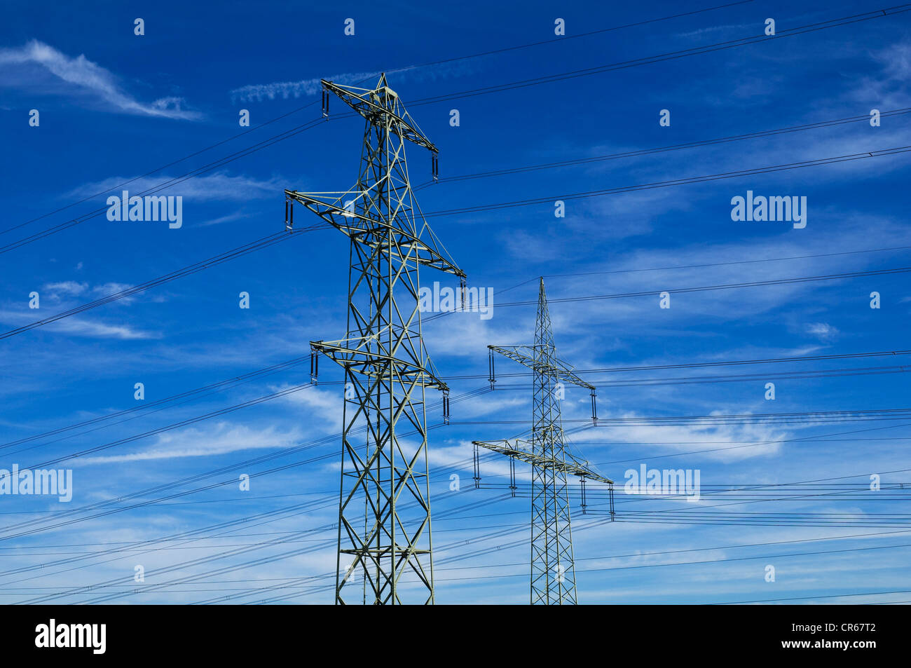 Two electricity pylons against blue sky with cirrostratus clouds - Stock Image