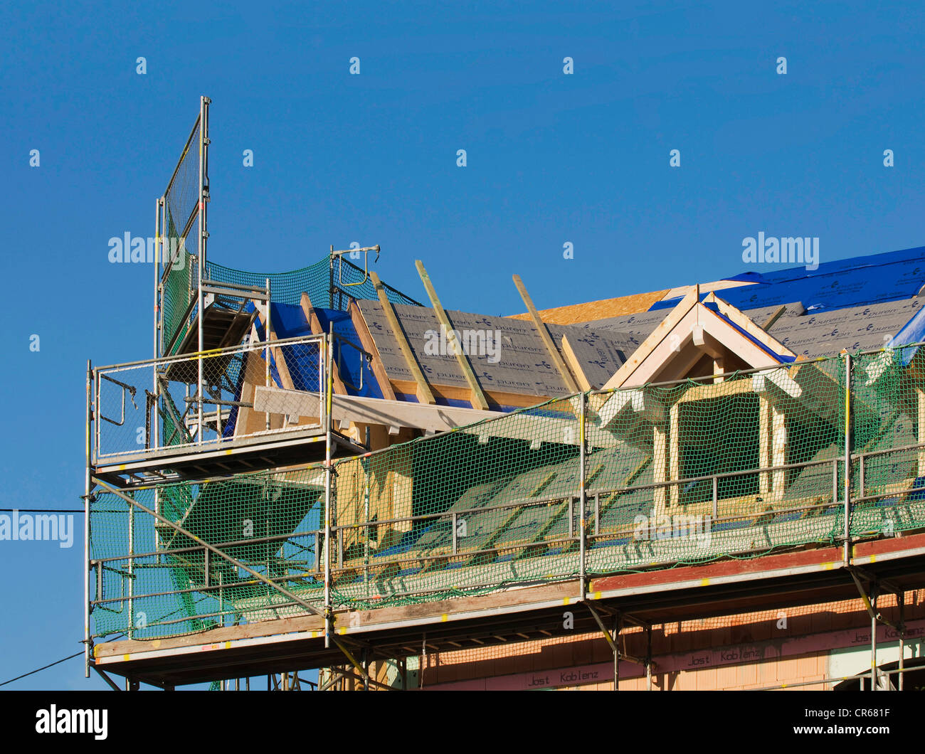 House with scaffolding, construction of a roof extension, modernisation - Stock Image