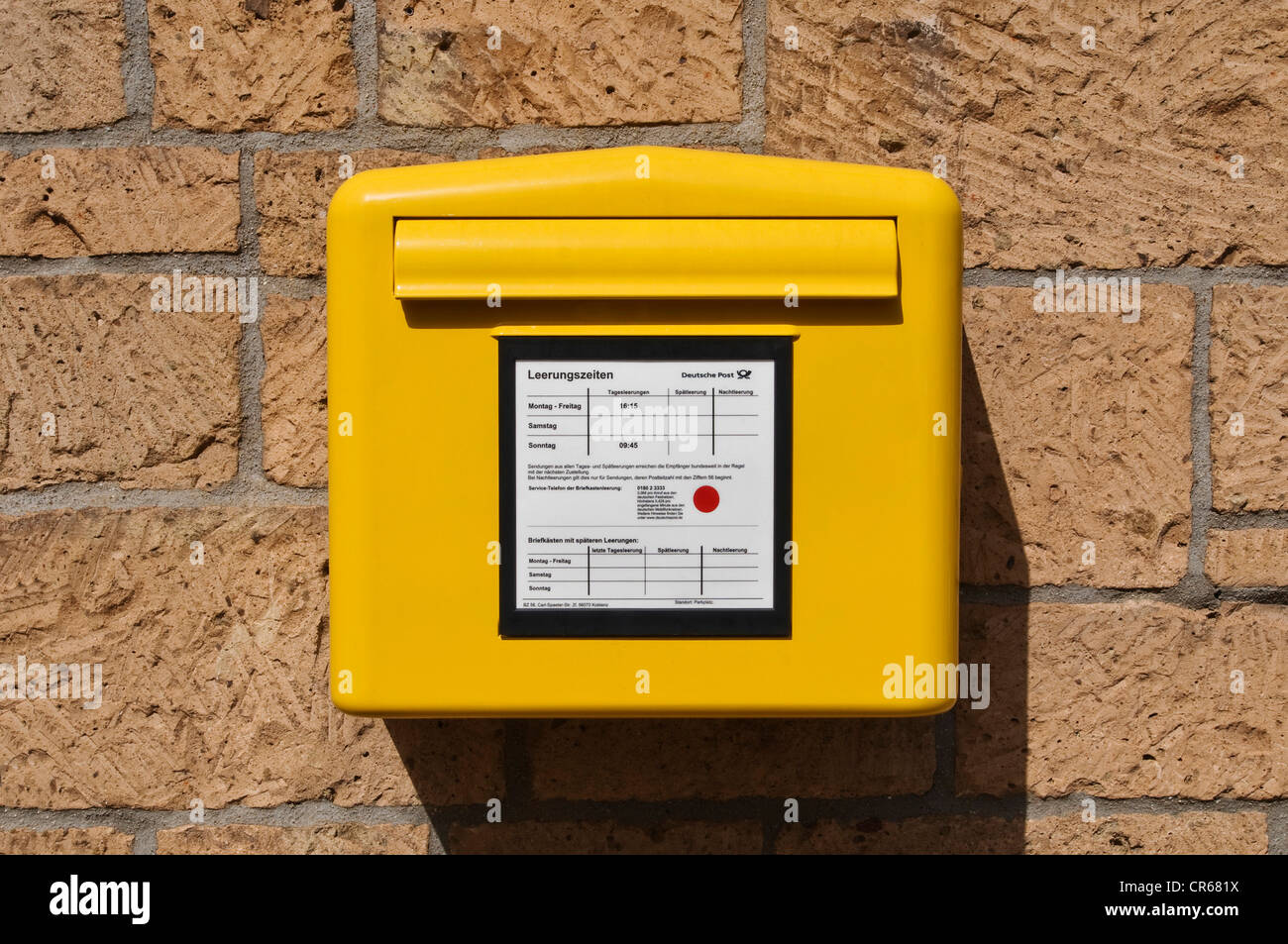Yellow postbox on a stone wall, Germany, Europe - Stock Image