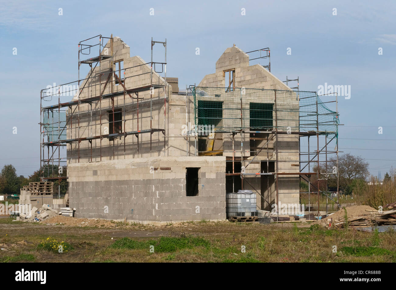 Shell construction surrounded by scaffolding, preparation for roof timbering, private residential building, PublicGround Stock Photo