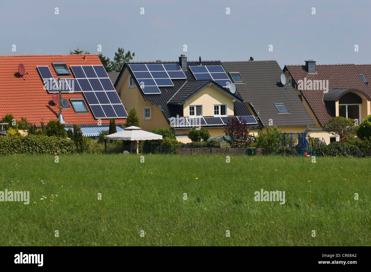Modern housing estate, multi-family houses with solar panels on the roof, in the countryside - Stock Image