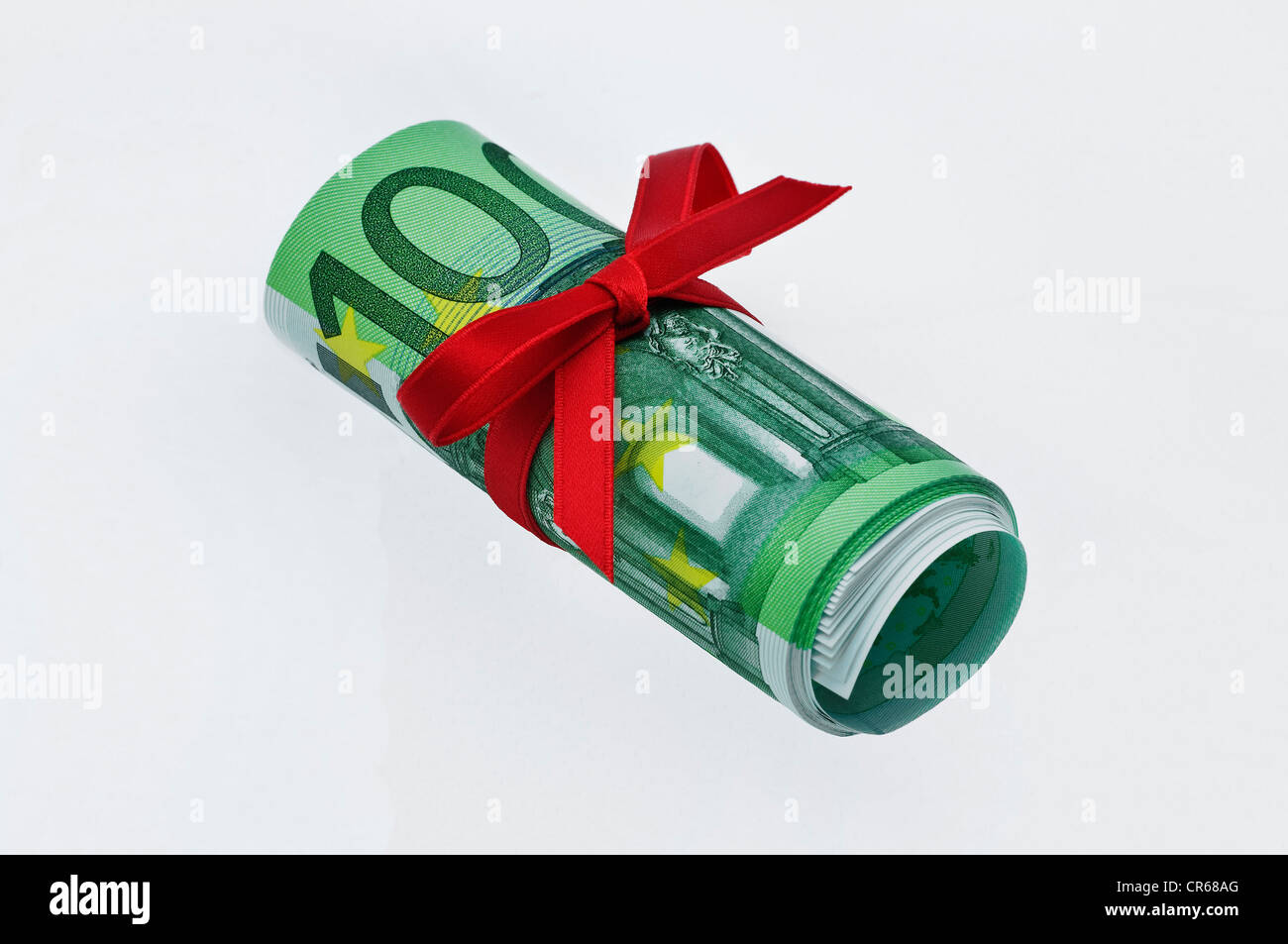 Rolled up 100-euro banknotes with a red ribbon, gift of money - Stock Image