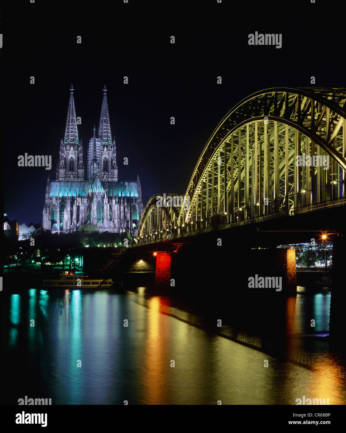 Arches of Deutz Bridge crossing the Rhine River in front of Cologne Cathedral at night, Cologne, North Rhine-Westphalia - Stock Image