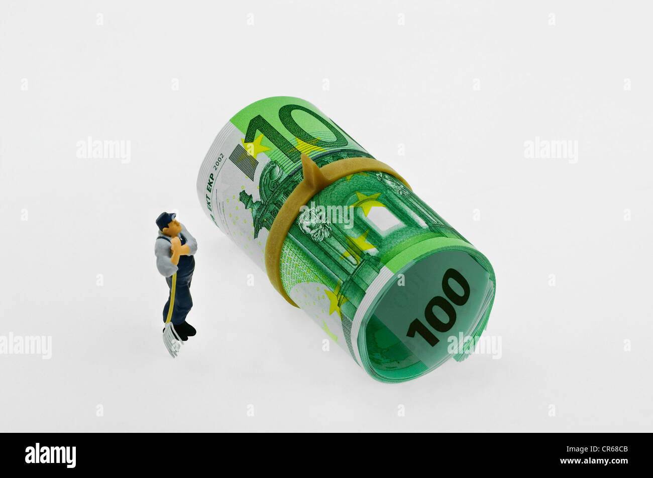 Miniature figure of a workman standing in front of roll of 100-euro notes and looking thoughtfully up - Stock Image
