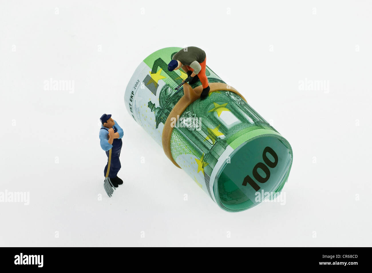 Two miniature figures of workmen, one using a tool on a roll of 100-euro notes, the second one looking up towards - Stock Image