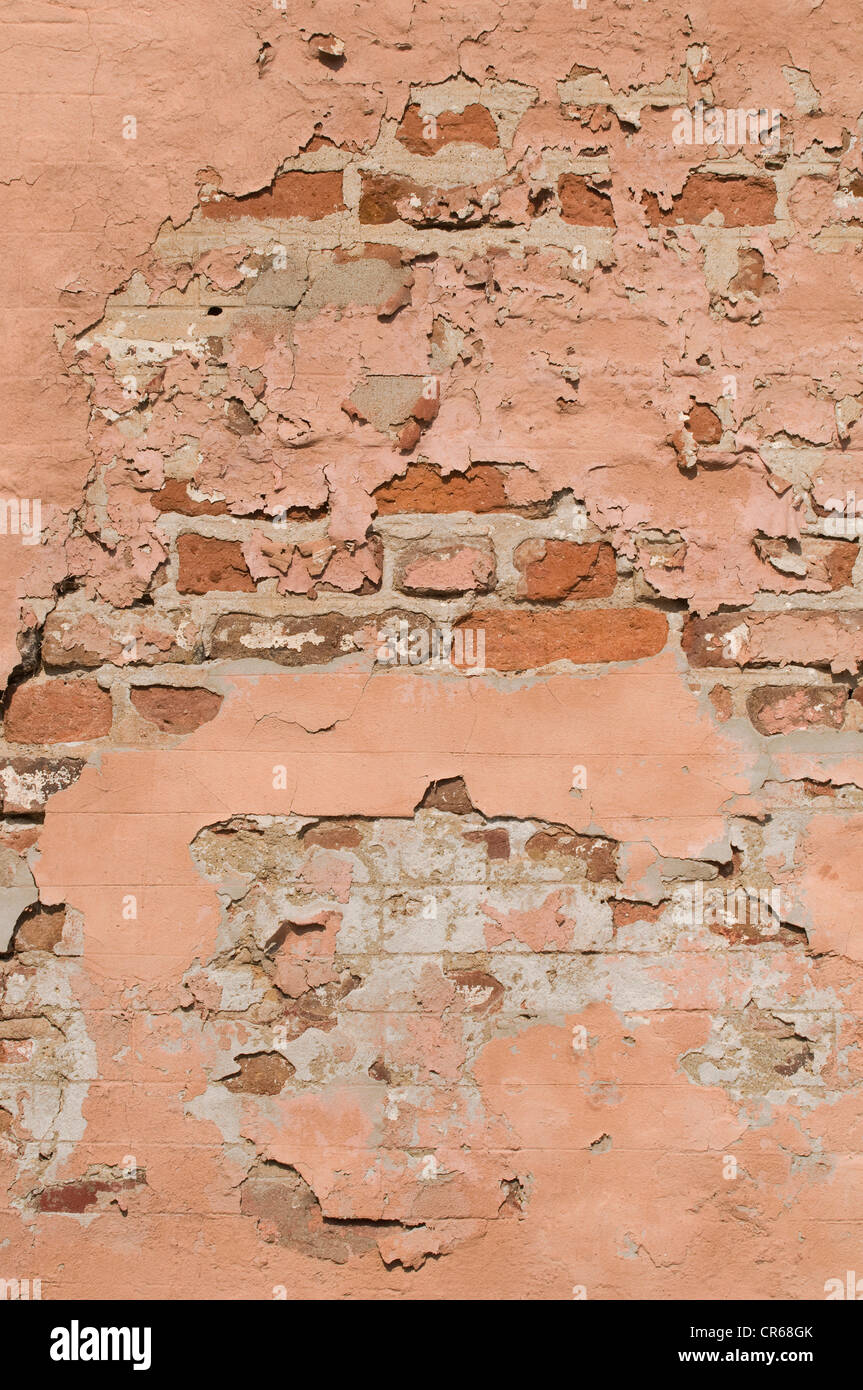 Brick wall with crumbling plaster, background - Stock Image