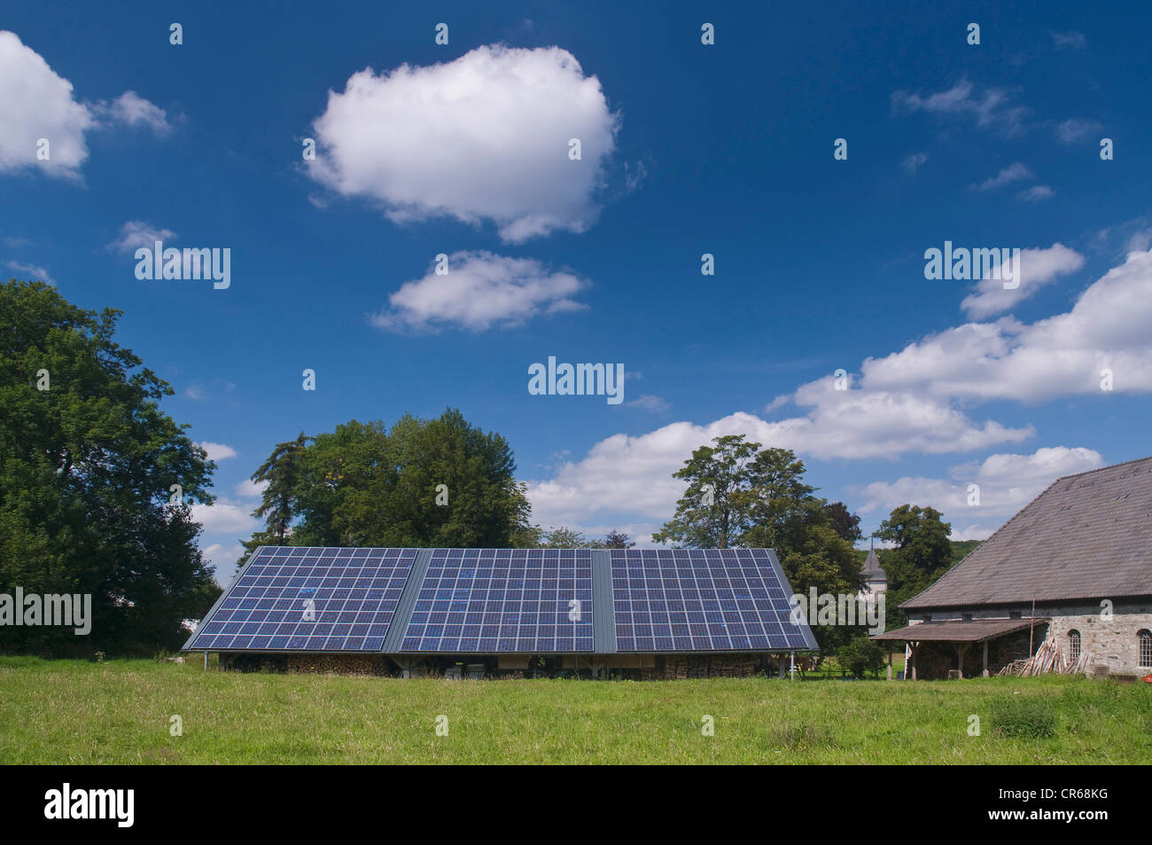Solar panels on the roof of a shed, next to a farm building, PublicGround - Stock Image