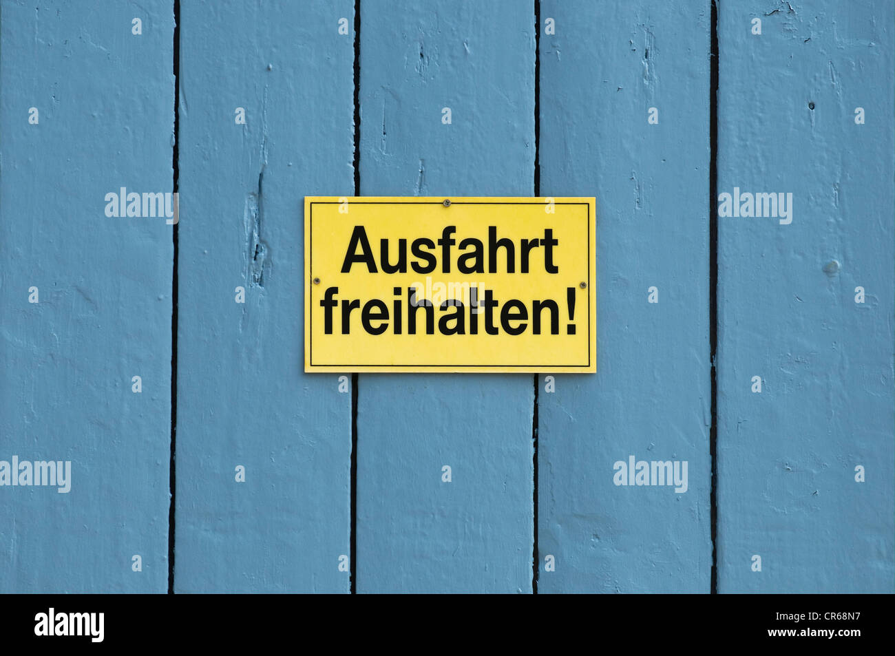 Sign, Ausfahrt freihalten or keep exit clear, on a blue door - Stock Image