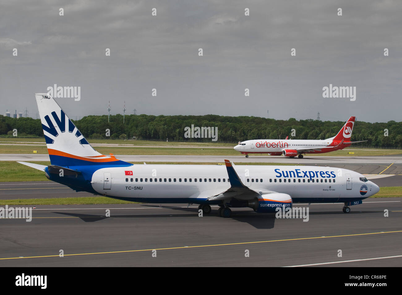 Boeing 737 800 of the Turkish SunExpress on the runway, behind an airberlin airplane, Duesseldorf International - Stock Image