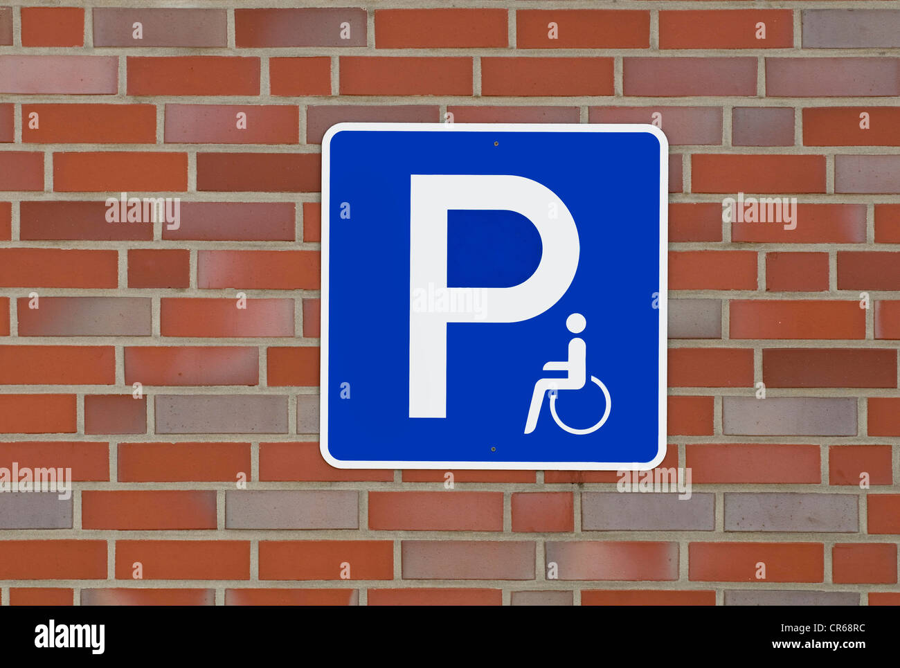 Sign with pictogram on brick wall: disabled parking - Stock Image