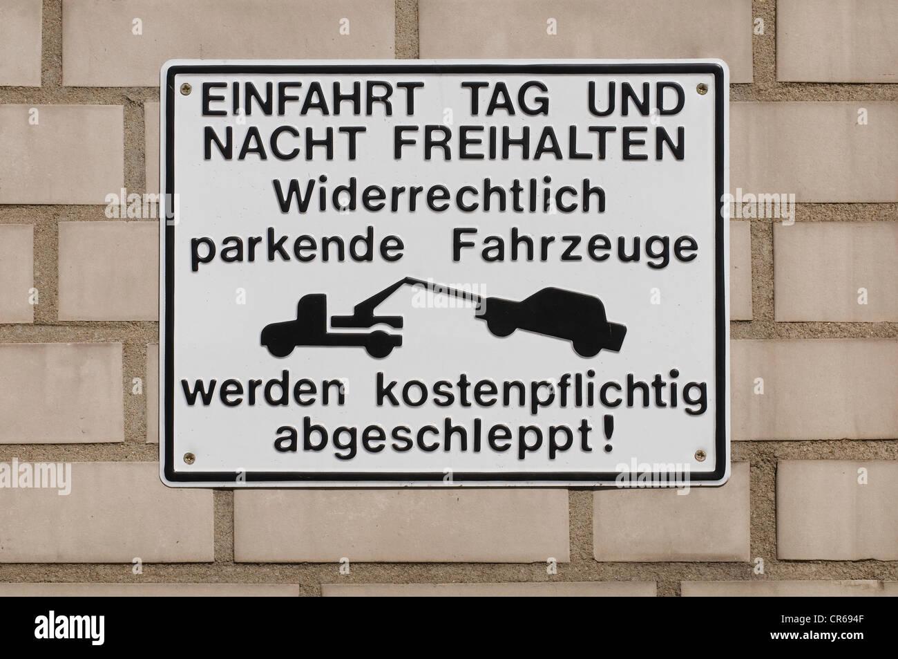 Sing on wall with tow truck pictogram, 'Einfahrt Tag und Nacht freihalten, widerrechtlich geparkte Fahrzeuge - Stock Image