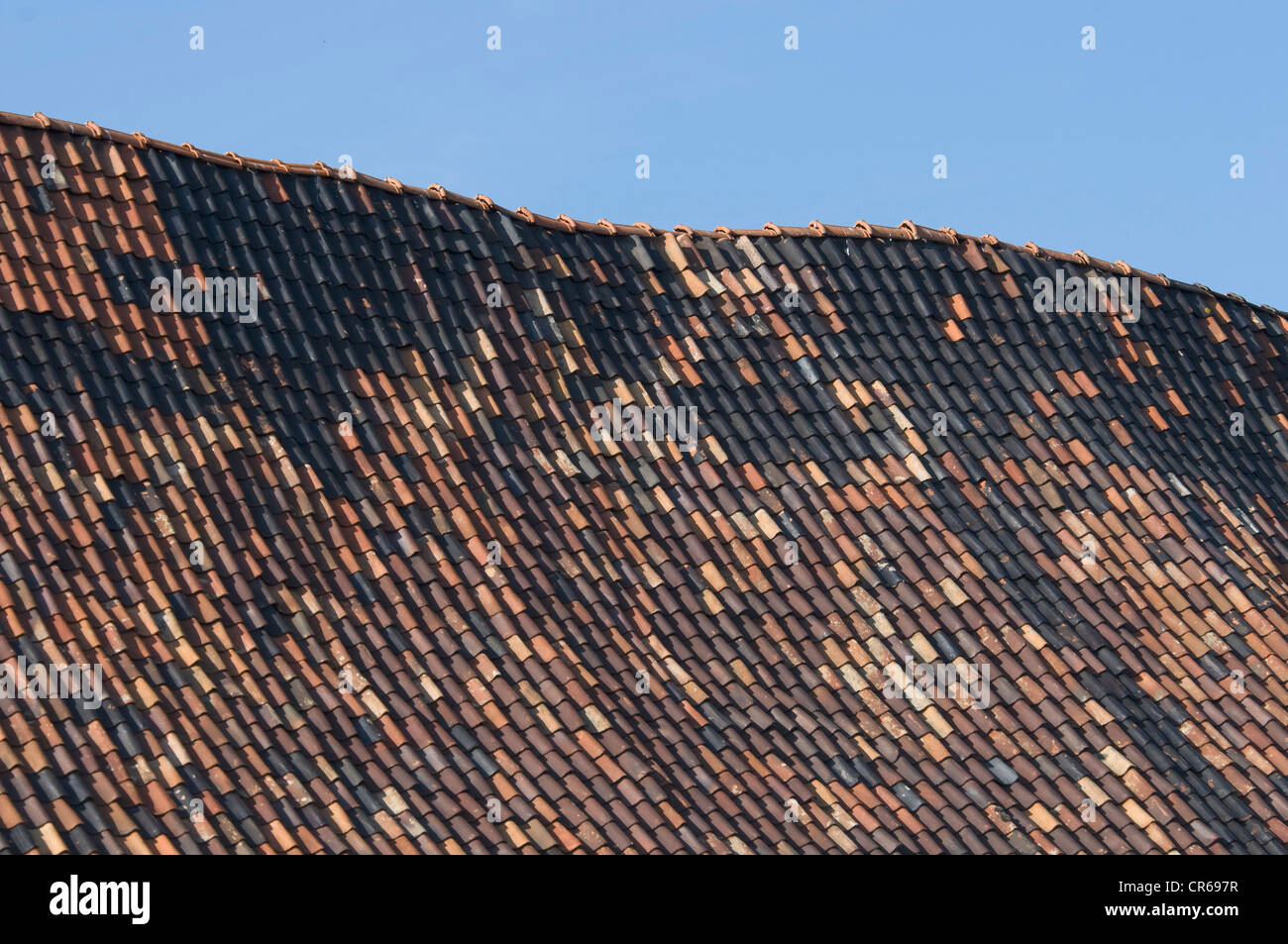 Old roof ridge, contorted gable, many replaced roof tiles, restoration - Stock Image